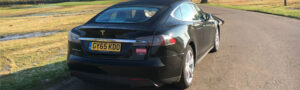 black tesla s driving in countryside